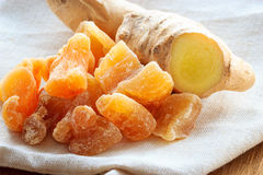Closeup root and candied ginger on rustic table Royalty Free Stock Photos