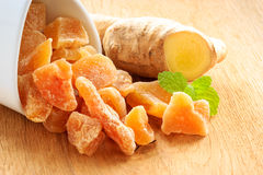 Closeup root and candied ginger on wooden table Royalty Free Stock Images