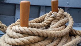 Closeup of rope around wooden pegs on sailboat. stock photo