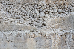 Closeup rough concrete wall with texture of pebbles Stock Images