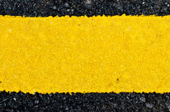 Closeup rough yellow paint on asphalt road Stock Photography