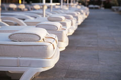 Closeup row of comfortable loungers near the swimming pool. At the recreation center Royalty Free Stock Images