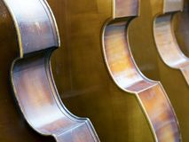 Closeup of row of double basses resting against a wall. Close together stock photography