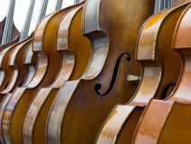 Closeup of row of double basses resting against a wall. Close together stock images