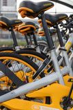 Vlaardingen, The Netherlands - february 4, 2018: closeup of a row ofyellow and silver public bikes. Closeup of row of oBikes in Vlaardingen near public transport Stock Images