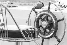 Yacht rudder in black and white. Closeup of rudder and chair in a luxury boat in black and white Royalty Free Stock Photos