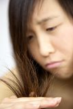 Closeup of ruined damaged hair of asian girl looking Stock Image