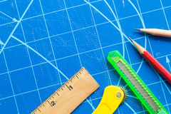 Closeup of ruler,scissors, cutter, pencil on blue cutting mat Royalty Free Stock Photo