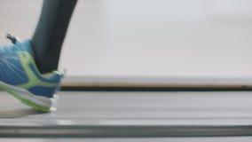Closeup running legs on treadmill in fitness gym. Fitness shoes running on treadmill. Close up fit people feet training in sport club stock video