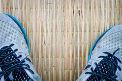 Closeup running shoes on traditional mat, copyspace on the middl Stock Image
