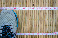Closeup running shoes on traditional mat with Measuring Tape, co royalty free stock photography