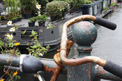 Closeup of rusty bike handles. A rusty bike parked on a bridge in Amsterdam. Flowers growing around the bike, and a houseboat seen in the distance below Stock Photography