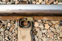 Closeup of rusty iron train track with railroad tie and pebbles. stock images