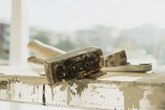 A metal mallet and a chisel on a working platform. Closeup of a rusty metal mallet and a cold chisel, on a working platform stained with paint and plaster, in a stock images