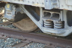 Closeup of Rusty Train wheel and track. Old train axel and shocks at rest Royalty Free Stock Image