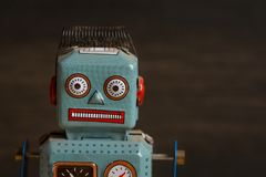 Tin toy robot against dark wood background Stock Photography
