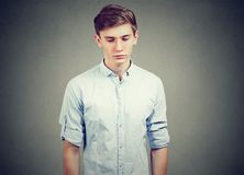 Closeup of a sad gloomy man looking down. Closeup of a sad gloomy casual young man looking down Stock Photography
