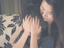 Closeup sad little boy being hugged by his mother at home. Parenthood, Love and togetherness concept Stock Photo