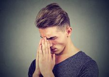 Sad young man with tensed face expression praying. Closeup of a sad man with tensed face expression praying looking down Royalty Free Stock Images
