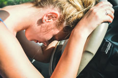 Closeup on sad tired beautiful lady driver in car leaning on the wheel Royalty Free Stock Photography