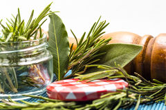 Closeup of sage and rosemary leaves in a jar. Near a pepper mill Stock Images