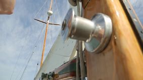 Closeup of the sail of a wooden antique Sail boat navigating in the ocean sunny day showing the wooden parts and. Sail boat navigating in the ocean sunny day stock video footage