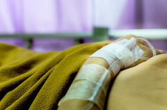 Closeup saline water line on a hand of patient and infusion line in a patients hand and body rehabilitation time. Stock Images