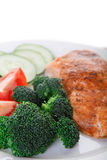 Closeup of Salmon Dinner. A dinner of baked salmon, broccoli, tomatoes and cucumber Royalty Free Stock Images