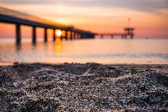 Closeup of sand on the beach. Blurred sunrise over a sea bridge in the background. Royalty Free Stock Image
