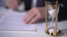 Closeup of sand clock measuring time, businessman signing important contract. Stock footage stock video footage