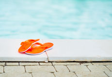 Closeup on sandals laying near swimming pool Royalty Free Stock Photo