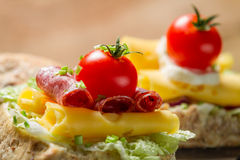 Closeup of sandwich with salami, tomato, cheese and lettuce Royalty Free Stock Image