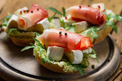 Closeup of sandwiches with parma ham, brie cheese and rocket sal Royalty Free Stock Photo