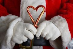 Closeup of Santa Claus hands holding two old fashioned candy canes forming a heart shape royalty free stock image