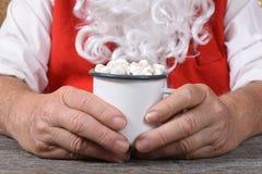 Closeup of Santa Claus holding a mug of hot fresh hot chocolate with marshmallows royalty free stock images