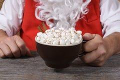 Closeup of Santa Claus holding a mug of hot fresh hot cocoa with marshmallows. royalty free stock photos