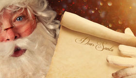 Closeup of Santa holding a Dear Santa scroll Stock Photography
