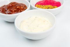 Closeup of sauces in white bowls Royalty Free Stock Photography