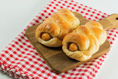 Closeup sausage baked in dough on wooden plate. Closeup sausage baked in dough on wooden plate put on fabric white, red. white background Stock Photo
