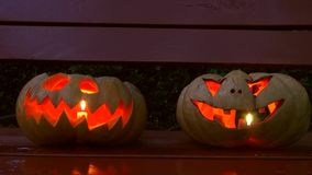 Closeup of scary halloween carved glowing pumpkins stock video footage