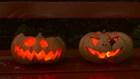 Closeup of scary halloween carved glowing pumpkins stock video