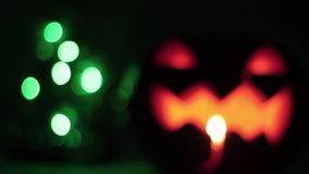 Closeup of scary holiday halloween carved glowing pumpkins. and Christmas tree. Flashing colored lights. Jack-O-Lantern. Closeup of scary holiday halloween stock video footage