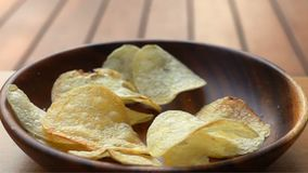 Closeup scene of potato chips fall into a wooden plate on the table