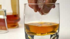 Closeup scene of putting ice cubes into a glass filled with whiskey.