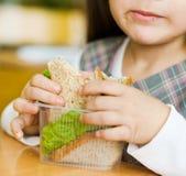 Closeup schoolgirl with sandwich in classroom Stock Photography