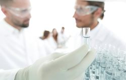 Scientist and assistant studying the solution in the tube. Closeup. scientist and assistant studying the solution in the tube Stock Images