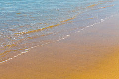 Closeup of sea foam on wet golden sand with copy space Stock Images