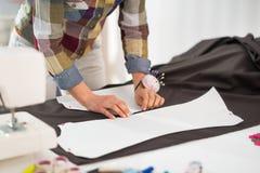 Closeup on seamstress making pattern on fabric Stock Image