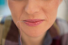 Closeup on seamstress with mouth needle in lips Stock Images