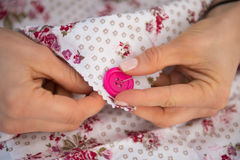 Closeup on seamstress sewing button Stock Photo